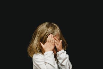 criança cobrindo rosto